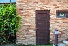 Alte Holztür und Brown-Backsteinmauer Stockfoto