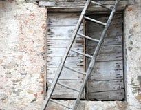 Alte Holztür und eine lange alte Leiter im Bauernhaus Lizenzfreies Stockbild