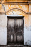 Alte Holztür und rustikale Betonmauer Stockbild
