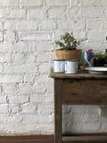 Alte Holztischdekoration Die Rückseite ist weiße Backsteinmauer lizenzfreies stockfoto