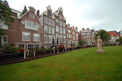 Alte Häuser und Skulptur auf dem Rasen, Amsterdam Lizenzfreies Stockfoto