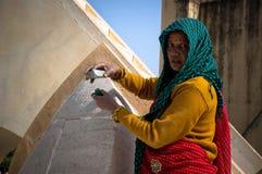 Alte indische Frau, die an dem Stein mit ursprünglichen Werkzeugen arbeitet Stockfotografie