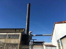 Alte Industriebauten mit Metallschornsteinen gegen einen tiefen blauen Himmel Lizenzfreie Stockbilder