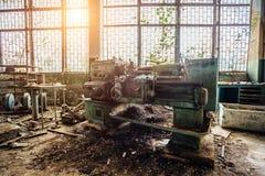 Alte industrielle Werkzeugmaschine Rostige Metallausrüstung in verlassener überwucherter Fabrik lizenzfreie stockbilder