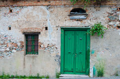 Alte italienische Steinhausfassade mit grüner Tür Stockfoto