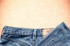 Alte Jeans auf Beton Stockfotos