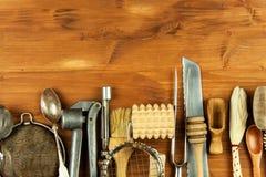 Alte Küchengeräte auf einem hölzernen Brett Verkauf der Küchenausrüstung Chef ` s Werkzeuge Stockfotografie