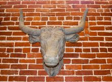 Alte Kühe gehen die Replik voran, die an einer rauen Backsteinmauer hängt stockbilder