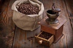 Alte Kaffeemühle mit Bohnen und Leinwand Lizenzfreie Stockfotos