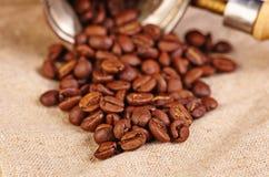 Alte Kaffeemaschine und Kaffeebohnen auf Segeltuch. Lizenzfreie Stockfotografie