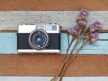 Alte Kamera der Weinlese mit Blume auf dem alten hölzernen lizenzfreie stockfotografie