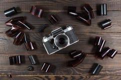 Alte Kamera und Filme sind auf der dunklen Holzoberfläche Stockbild