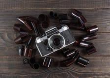 Alte Kamera und Filme sind auf der dunklen Holzoberfläche Stockfoto
