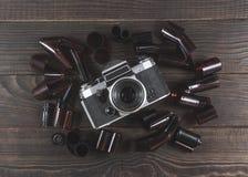 Alte Kamera und Filme sind auf der dunklen Holzoberfläche Stockfotografie