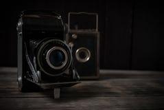 Alte Kameras, die auf alten rauen Brettern stehen Stockfotos