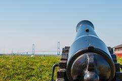 Alte Kanone, die in Richtung zur großen Gurt-Brücke zeigt Lizenzfreie Stockbilder