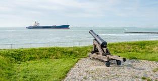 Alte Kanone gerichtet auf einen überschreitenen Frachter Stockbilder