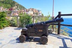 Alte Kanone und Cinque Terre-Dorf Manarola mit bunten Häusern und Mittelmeer Lizenzfreies Stockfoto