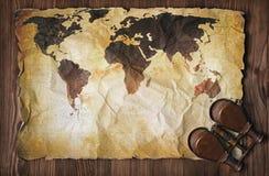 Alte Karte der Welt auf gelbem Retro- beflecktem Papier mit Weinleseferngläsern Stockfotografie
