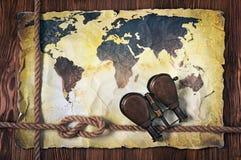 Alte Karte der Welt auf gelbem Retro- beflecktem Papier mit Weinleseferngläsern und des Knotens des Seils Stockbilder