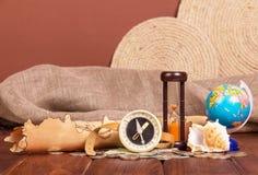 Alte Karte, Kompass, Kugel, Sanduhr und Münzen auf braunem Hintergrund Lizenzfreie Stockfotos