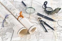 Alte Karten in den Rollen mit Vergrößerungsglas und Kompass Lizenzfreie Stockfotos