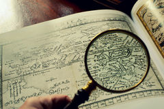 Alte Karten und ein Vergrößerungsglas Stockfotos