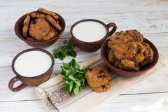 Alte keramische Schalen Milch und frisch gebackene Hafermehlrosinenplätzchen im Lehm rollen Lizenzfreie Stockfotografie