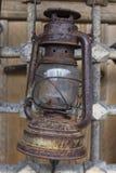 Alte Kerosinlampe, die auf einem Metallgitter hängt Lizenzfreie Stockfotografie