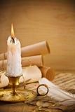 Alte Kerze auf Tabelle mit Rollen des Papiers Stockbilder