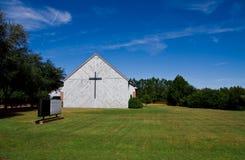 Alte Kirche auf dem Gebiet mit leerem Zeichen und Kreuz Lizenzfreies Stockfoto