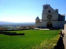 Alte Kirche mit grünem Feld auf dem Hügel von Assisi Stockfotos