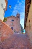 Alte Kirche und schmale Straße. Monticello D'Alba, Italien. Lizenzfreie Stockfotos