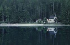 Alte Kirche und Waldland reflektiert im See Stockfotos