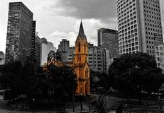 Alte Kirche unter modernen Gebäuden Stockfotos