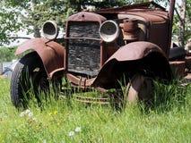 Alte Klapperkiste, die weg im hohen Gras verrostet Lizenzfreie Stockfotografie