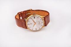 Alte klassische Armbanduhr für Mann mit braunem Bügel auf Weiß Stockfotografie