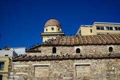 Alte klassische kleine Kirche im Erdtonnaturstein mit Tauben auf Terrakottadachplatte mit klarem blauem Himmel und modernem Gebäu Stockfotos