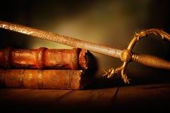 Alte Klinge mit Lederbüchern auf Holztisch Lizenzfreies Stockfoto