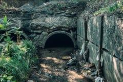 Alte konkrete Abflussrohre mit flüssigem Abwasser-, Abwasser- oder Kanalisationstunnelrohr mit Wasserstrom Stockbilder