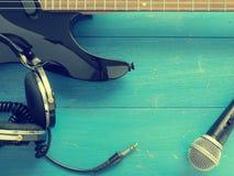 Alte Kopfhörer und Gitarre auf Holz Stockbild