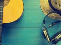 Alte Kopfhörer und Gitarre auf Holz Stockfoto