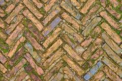 Alte Kopfsteinsteine in einem Fischgrätenmustermuster Stockfotografie