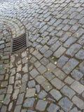 Alte Kopfsteinsteinstraßenstraße und -abwasserkanal Lizenzfreie Stockfotografie