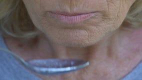 Alte kranke Frau, die kaum Brei, schlechte Sorgfalt von Leuten im Pflegeheim, Verzweiflung kaut stock footage
