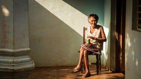 Alte kubanische Frau auf Stuhl ein Bier genießend Stockfotografie
