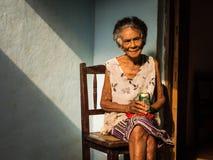 Alte kubanische Frau auf Stuhl ein Bier genießend Lizenzfreies Stockfoto