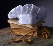 Alte kulinarische Bücher, Chefhut und hölzerne Löffel Stockbilder