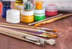 Alte Kunstbürsten und -farben auf einem hölzernen Hintergrund Stockbild
