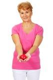 Alte lächelnde Frau, die rotes Spielzeugherz hält Stockbild